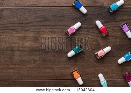 nail polish bottles on brown wooden table