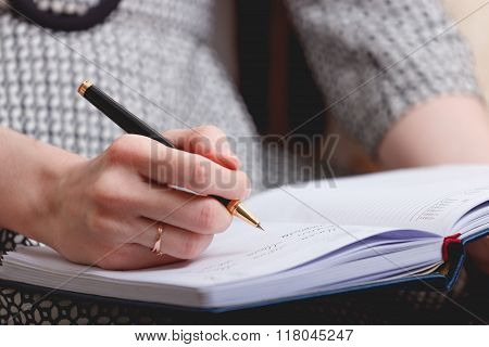 Beautiful girl looking serious - writting on her notebook