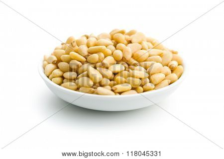 pine nuts in bowl on white background