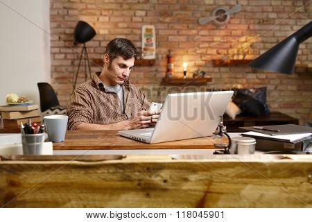 Casual man using mobilephone, sitting at desk, having laptop, texting.