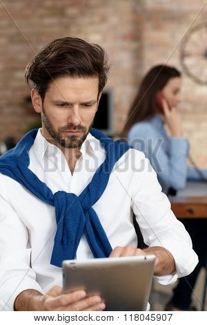 Serious businessman working with tablet computer.