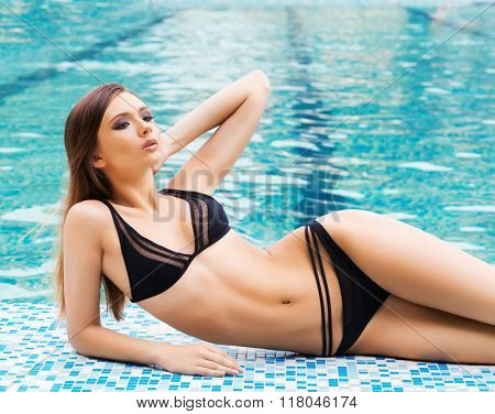 Young and sporty woman in swimsuit. Girl relaxing in a pool.