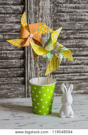 Easter Decorations - Homemade Paper Pinwheels And Ceramic Easter Bunny On A Light Rustic Wood Backgr