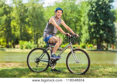 Active senior man riding a bike in park on a beautiful summer day shot with tilt and shift lens