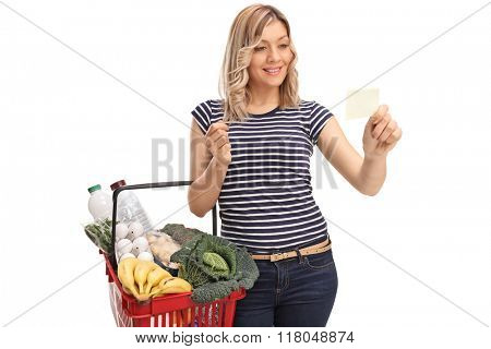 Woman holding a shopping basket and reading a piece of paper isolated on white background