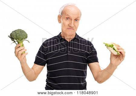 Indecisive senior man holding a piece of broccoli in one hand and a sandwich in the other isolated on white background