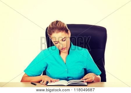 Female doctor sitting behind the desk and writing a notes