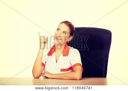 Smile female doctor sitting behind the desk and pointing up