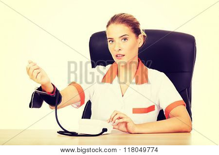 Doctor sitting behind the desk holding blood pressure gauge