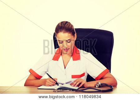 Doctor sitting behind the desk and writing a notes