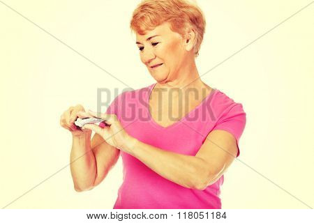 Smiling senior woman holding toothpaste and toothbrush