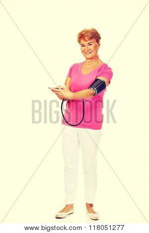 Smiling senior woman measuring blood pressure