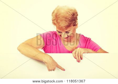 Senior woman pointing for something on empty banner