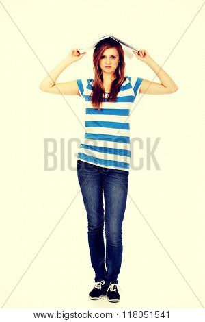 Teenage woman with notebook on head