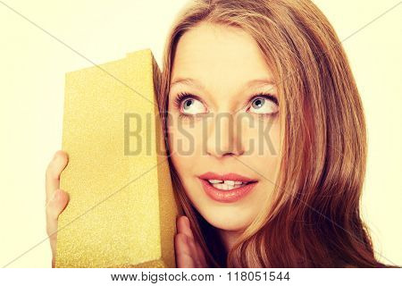 Young woman shaking the gift box