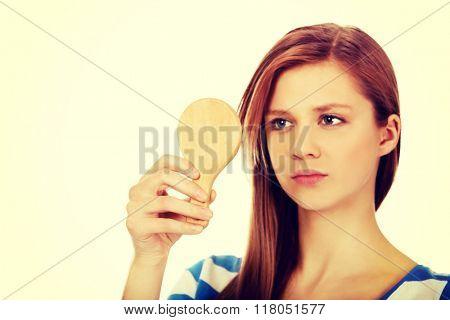 Teenage beautiful woman looking in a mirror