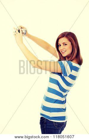 Happy teenage woman taking selfie with classic slr camera