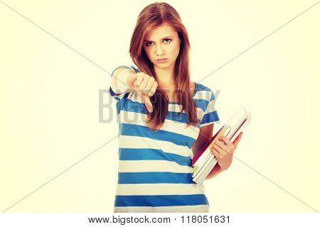 Teenage woman holding a books and shows thumb down