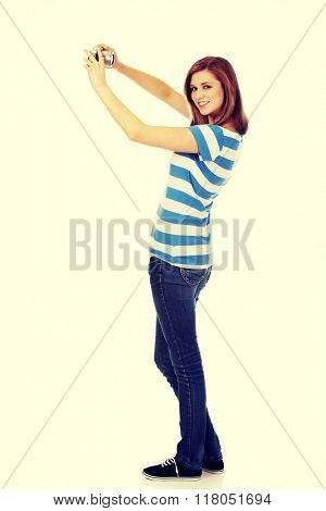 Happy young woman taking selfie with classic slr camera