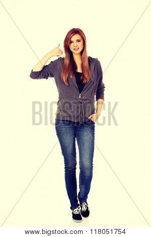 Teenage woman gesturing call me sign