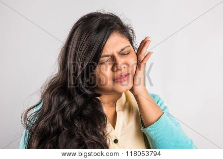 Closeup portrait young indian woman with sensitive tooth ache problem about to cry from pain touchin