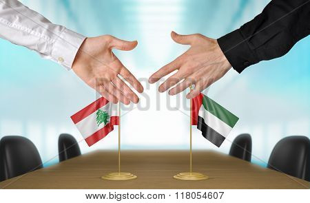 Lebanon and United Arab Emirates diplomats shaking hands to agree deal