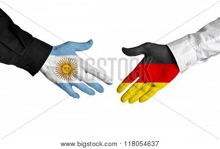 Argentina and Germany leaders shaking hands on a deal agreement
