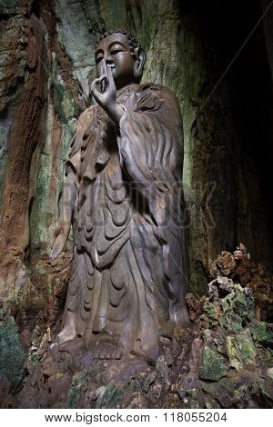 Sculpture of standing Buddha in the cave Tang Chon in the Marble mountains. Vietnam