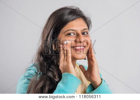 indian woman applying cream to face, skincare concept, Skin care asian lady putting face cream, indi