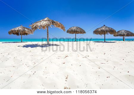 Beach Umbrellas made of palm leafs on exotic beach