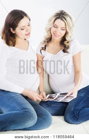 Two young beautiful pregnant women watching ultrasound scans of their embryos.