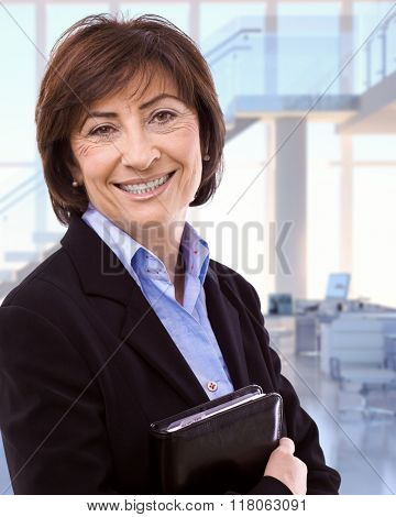 Portrait of happy caucasian brunette senior businesswoman at business office. Smiling, looking at camera, woman suit, copyspace.