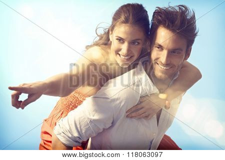 Romantic loving couple piggyback on summer holiday.