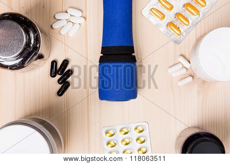 Sport supplements and a barbell on a wooden background