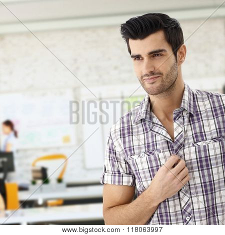 Closeup of casual young caucasian man at office smiling.