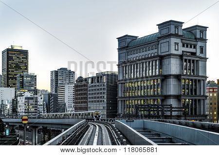 Tokyo Monorail At Dusk With Buildings And Train Desaturated