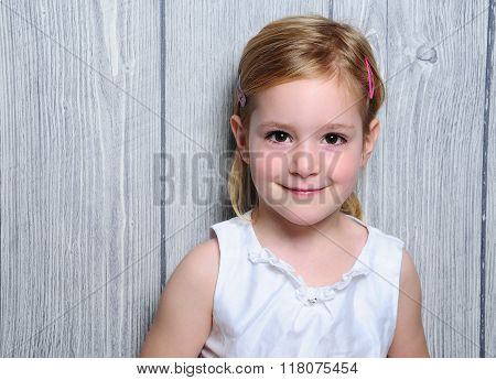 Portrait Of A Cute Four-year Smiling Blonde Girl In White Dress