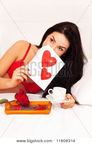 In Love With A Beautiful Young Girl Lying In Bed With Gifts, Cards, Hearts, Coffee, Roses. Feast Day
