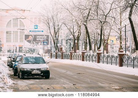 Cars parking in the avenue of Victory in Gomel. Snowy street in