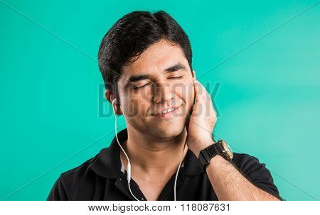 indian man with headphones, indian boy with ear plugs and mobile phone, indian man enjoying music, a