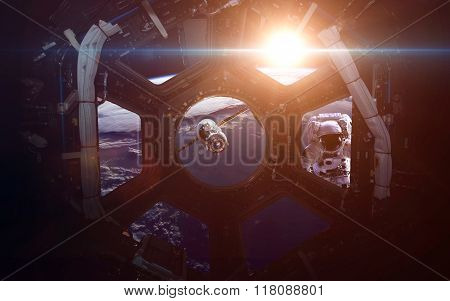 A round window on a space station with a view of Earth below. This image elements furnished by NASA