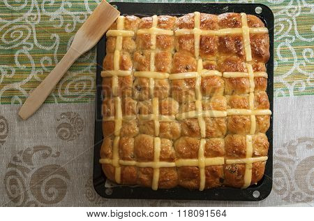 Top View Of Homemade Easter Hot Cross Buns On Baking Pan Against Colorful Tablecloth