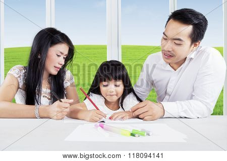 Child Learning At Home With Her Parents