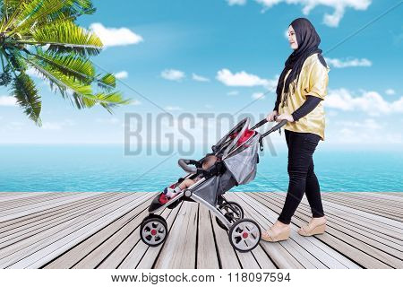 Mother Pushing Stroller At Beach