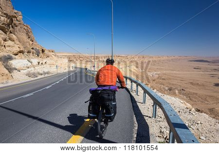 Happy biker relax on beautiful road in Israel desert. Sunny hot day