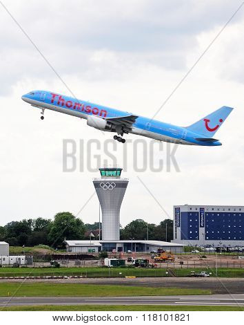 Aeroplane taking off over control tower.