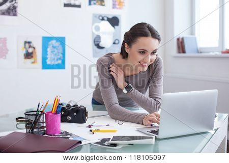 Attractive young photo artist is using a laptop
