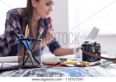 Pretty female photo artist is working in office