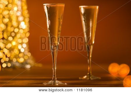 Close-Up Of Fluted Champagne Glass'S & Glowing Golden Lights