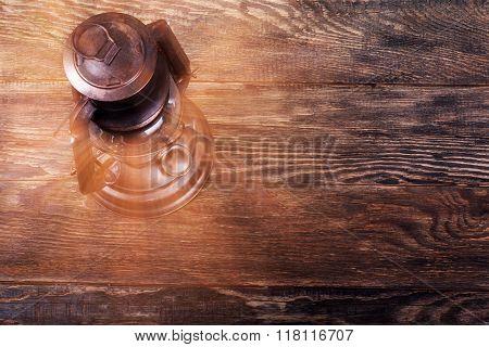 Old Rusty Kerosene Lantern On Wooden Floor